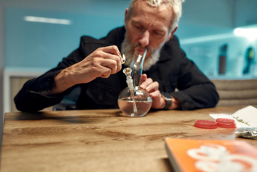 Senior man lighting a buy glass pipe in Australia